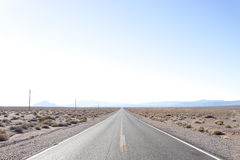 Straight Desert Highway in California. A desert highway leading to a distant mountain range in California. The plan is very flat and only small shrubs manage to Stock Image