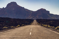Straight desert road with mountains on background Stock Photo