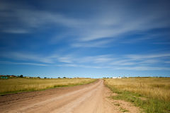 Straight dirt road. Long straight dirt road stretches into the distance Royalty Free Stock Photos