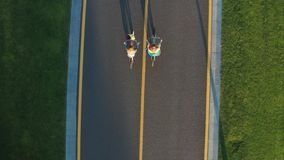 Drone shot of gay couple biking along bicycle path. Straight down aerial view of young lgbt couple spending summer vacation riding bicycles on bike lane. Happy stock video