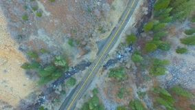 Straight down view of a mountain road in the forest with a river rushing by and cars passing on the road. Straight down aerial view of a mountain road and a stock footage