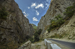 Straight empty highway leading into Xinalig village. Beautiful landscape of big Caucasus mountains and road country road with blue Royalty Free Stock Photo