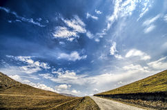 Straight empty highway leading into Xinalig village. Beautiful landscape of big Caucasus mountains and road country road with blue Stock Image