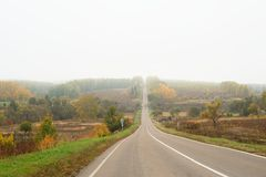 Straight empty misty road going up in autumn in the country Royalty Free Stock Photos