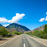 Straight and empty mountain road. Scenic asphalt road leads through mountain valley Stock Photos