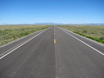 Straight empty road. Empty highway 60 cuts straight across the Plains of San Agustin, New Mexico to the horizon Stock Images