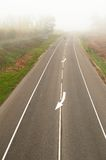 Straight empty road in autumn heavy mist in the country Royalty Free Stock Photo