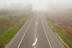 Straight empty road in heavy mist in autumn morning Stock Image