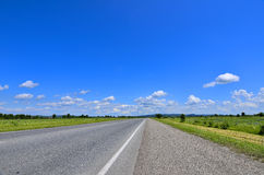 Straight empty road running to horizon. Straight empty road and roadside with cuttings grass running to horizon through meadows. Blue sky with white clouds and Stock Photography