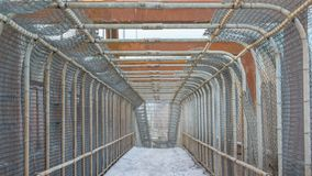 Straight fenced in cage-like walking path bridge over interstate - snowy winter overcast day - cement and metal are weathered, gri stock photos