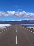 Straight, flat empty road. A view down the centerline of a long, straight, flat, deserted two-lane highway across a large salt flat with mountains in the Royalty Free Stock Photos