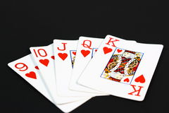 Straight Flush. Five playing cards, all hearts, fanned out in a straight flush on a black background Stock Images