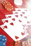 Straight Flush. Beams of heavenly light illuminate a winning hand, straight flush of hearts royalty free stock photo
