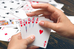 Straight flush in female hands. Well-conditioned female hands holding playing cards with poker strongest combination - royal flush Stock Photos