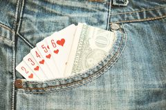 Straight Flush playing cards and money in pocket. Jeans Royalty Free Stock Image