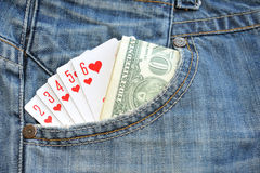 Straight Flush playing cards and money in pocket. Jeans Royalty Free Stock Images