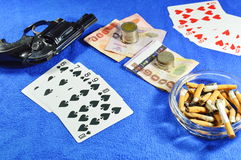 Straight flush win poker game and gun with cigarette on blue velvet table Royalty Free Stock Photos