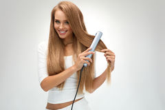 Straight Hair. Beautiful Woman Ironing Long Blonde Hair Royalty Free Stock Photo