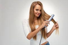 Straight Hair. Beautiful Woman Ironing Long Blonde Hair Royalty Free Stock Photos