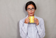 Straight hair brunette lady blowing hot drink. While holding mug in formal clothing and glasses and looking at camera on grey texture background Stock Images