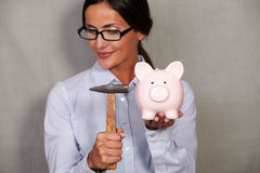 Straight hair female holding hammer and piggy bank Royalty Free Stock Photo