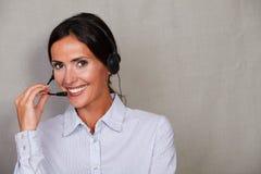 Straight hair lady operator using headset Royalty Free Stock Image
