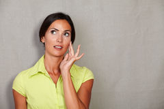Straight hair lady thinking with fingers on face Stock Photo