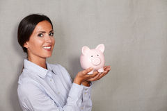 Straight hair woman holding pink piggy bank Royalty Free Stock Photos