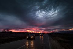 Straight road to sunset close to twilight with cars passing royalty free stock photography
