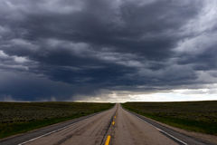 Straight Highway and Storm Cloud. Straight highway traveling up a hill and disappearing over the horizon with a threatening dark storm cloud overhead Royalty Free Stock Images