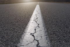 Straight line on asphalt full of cracks Royalty Free Stock Photos
