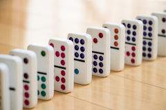 Straight Line of Colorful Dominoes on Wooden Floor Royalty Free Stock Image