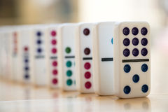 Straight Line of Colorful Dominoes on Wooden Floor Stock Photos