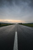 Straight lonely road at sunset after storm Stock Photos