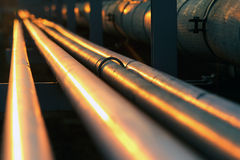 Straight long pipe line in oil refinery during sunset Stock Images