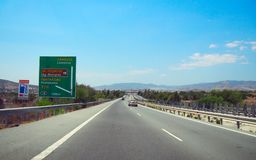 Straight motorway in Cyprus with road sign. Bright sunny summer day royalty free stock photography