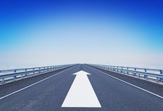 Straight motorway with a forward arrow. Concept of moving ahead stock image