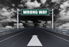 Straight motorway with a text Wrong Way on the road sign. Road to Dark stock photos