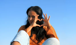 Straight from my heart. Beautiful brunette in orange skirt, showing her heart-shaped hands. Isolated on blue sky Royalty Free Stock Photography