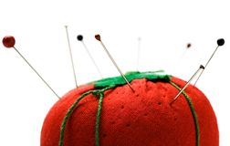 Straight pins stuck on pin cushion. Straight pins stuck on a pin cushion isolated over white Royalty Free Stock Image