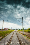 Straight railroad with dark cloudy sky Stock Photos