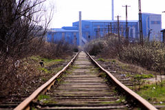 Straight railroad going to old blue factory Stock Photos