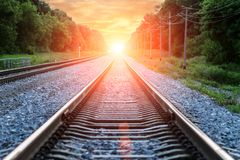 Straight Railroad into sunset with clouds in sky Royalty Free Stock Images