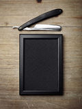 Straight razor and black picture frame on wood desk Stock Photo