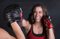 Straight Right. Beautiful young smiling woman doing a straight right punch into a focus mitt Royalty Free Stock Photography