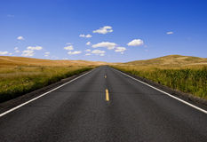 Straight road. Going through farmland in rural north america Stock Photos