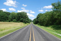 Straight Road. That appears to enter a forest on the horizon Royalty Free Stock Images