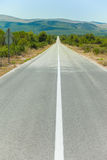 A straight road. Down the hill through the vegetation Royalty Free Stock Photos