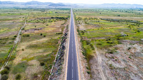 Straight road from above. Aerial view of a straight road in the valley Stock Images