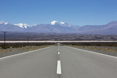 Straight road and Aconcagua mountains, North of Argentina. Straight paved road with the Pampa of El Leoncito and the Aconcagua mountain against a blue sky, San Royalty Free Stock Photo